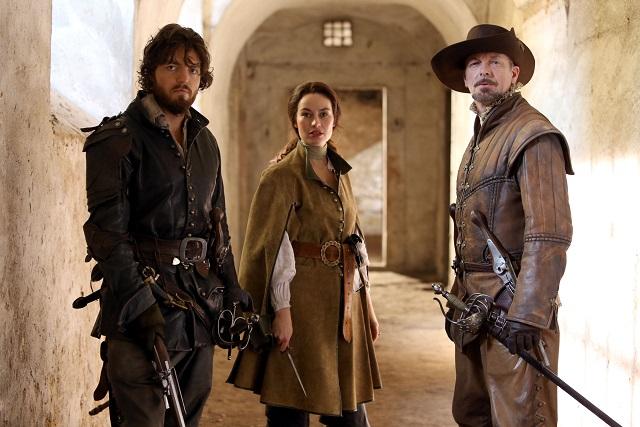Athos (TOM BURKE), Milady (MAIMIE MCCOY) and Captain Treville (HUGO SPEER) - Image Credit: BBC/Dusan Martinek